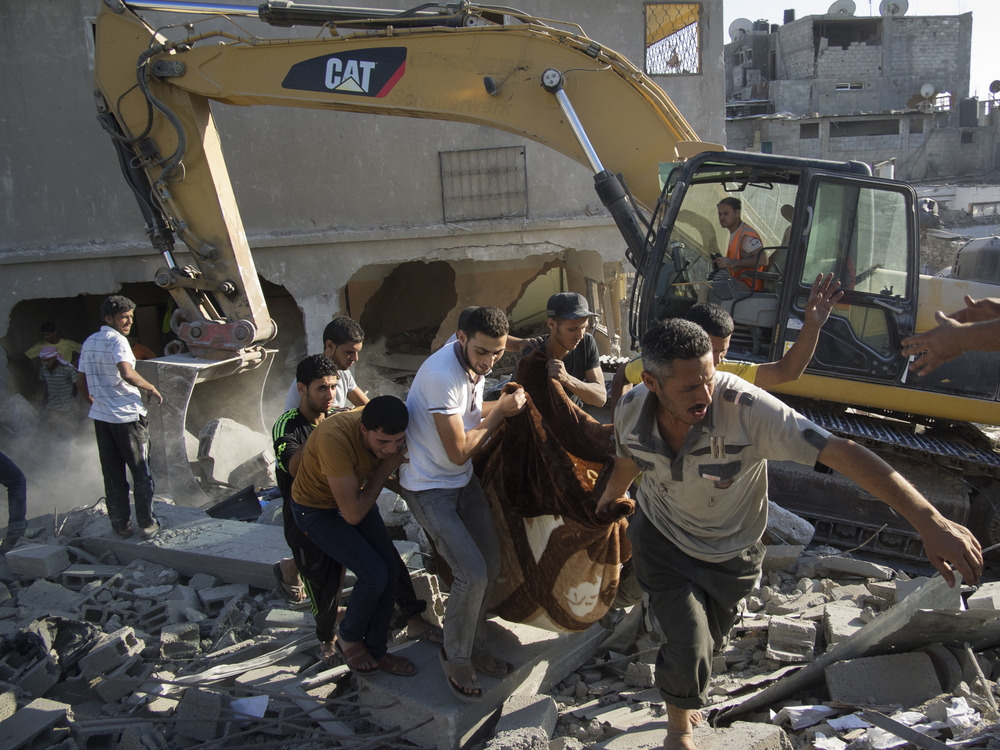 Men recover the body of a victim killed by an Israeli airstrike in Beit-Hanoun, July 26, 2014.