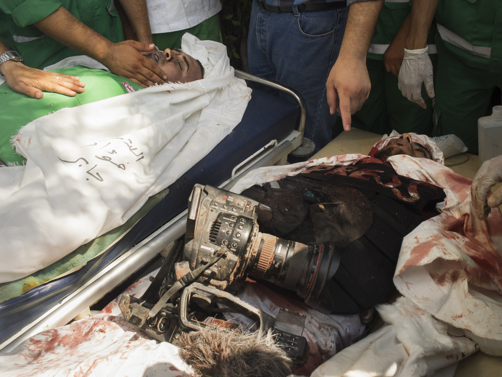 The bodies of paramedic Fuad Jaber and cameraman Khaled Hammad killed by an Israeli airstrike on the ambulance they were riding in, while trying to rescue the wounded in  Shuja'iyya  district, Gaza City, July 20, 2014.