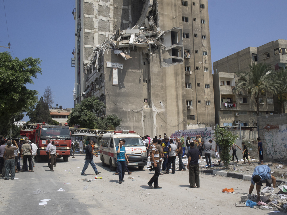 Palestinian rescue personnel inspect the damaged Al-Salam tower after an overnight Israeli strike, 15 people were killed and 30 injured, Gaza City, 22 July, 2014.