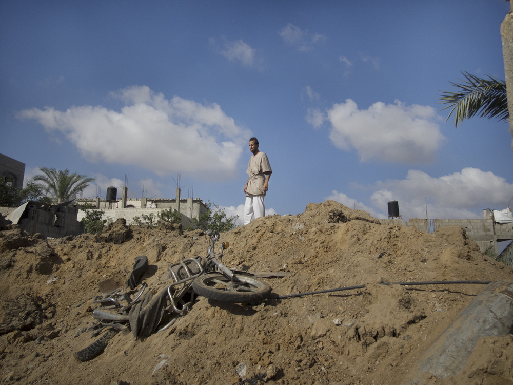 A man looks into the hole left by an Israeli airstrike. Rafah, July 26, 2014.
