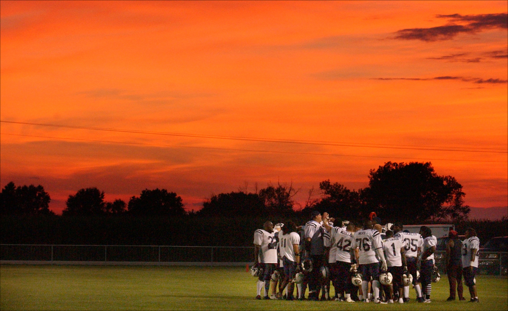 The St. Louis minor league football team The Spirits huddle on the field during halftime under a blood red sky.