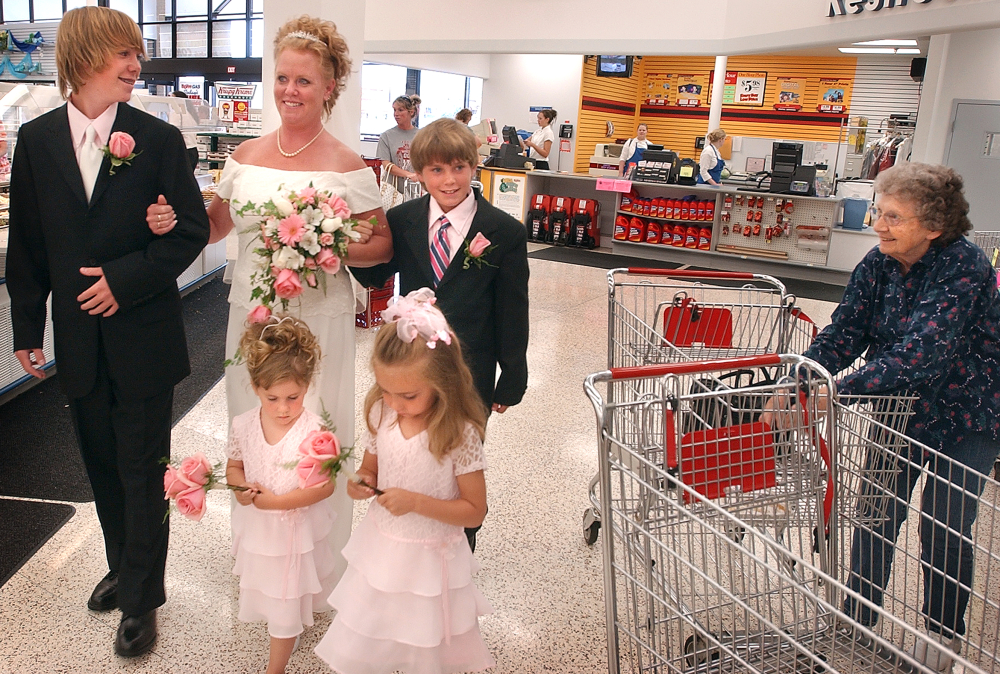 Diane Roderick drew a bit of attention on a Saturday at the HyVee grocery store in Quincy, Il. as she prepared to go down the aisle. Her sons Stuart Roderick, left, and Spencer Roderick, right, accompanied their mother and flower girls Morgan Fleer, left, and Madison Lane, right, as they walked to the store's deli where Roderick's husband to be, HyVee employee Tom Lane was waiting with a handful of guests. The wedding ceremony was hosted by HyVee after the employees got wind that the two, who met at the store, had plans to marry.