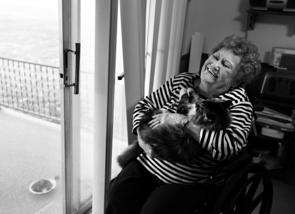 """Bonnie Chapman cuddles her cat as she laughs about how she now gets around in her wheelchair after having to have a leg amputated. """"I'm still moving. I'm still here. This ain't going to stop me."""""""