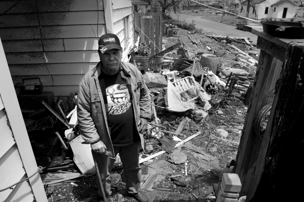 Fred Coombes stands in his yard in Joplin, Mo. after one of largest tornadoes in the United States destroyed his home and property.