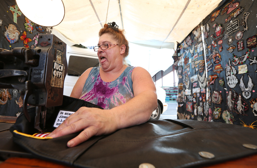 """Miss Chrissy, """"The Patch Queen,"""" and owner of Bee-Bad Leathers, sewed patches onto a leather vest for a customer in her booth. Miss Chrissy, who does not go by a last name, said she has been sewing patches onto biker leathers for 30 years."""