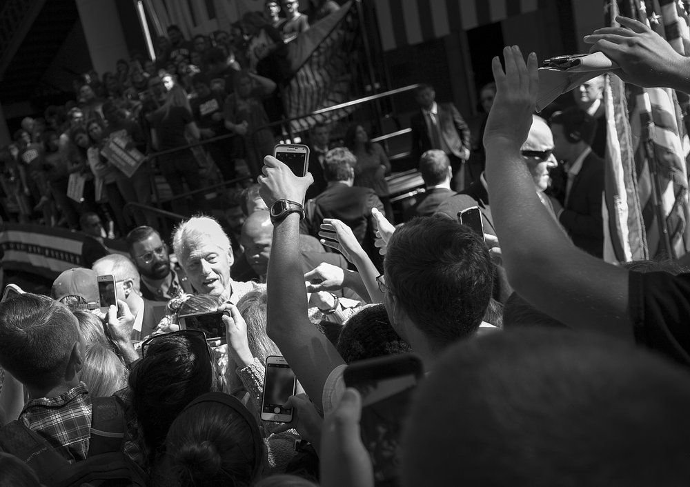 At the end of a speech in Athens, Ohio, Former President Clinton shook hands with people who crowded to the front for selfies, handshakes and photos.