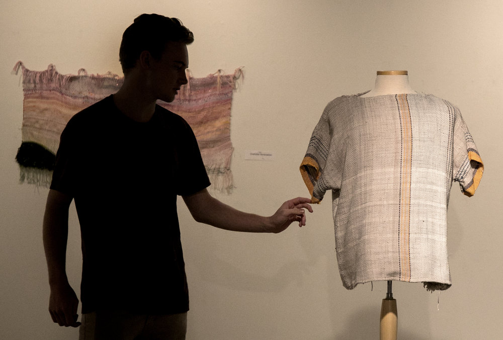 Charlie Day touches and adjusts a woven fiber art shirt that he made during a gallery opening.