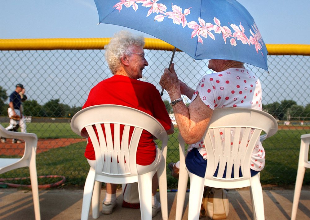 Recently widowed, Letha Althoff, left, and Florence Lummer decided not to stop going to the Quincy Gems games just because their husbands had died. The two never miss a game and always take turns holding the umbrella to block the summer sun.