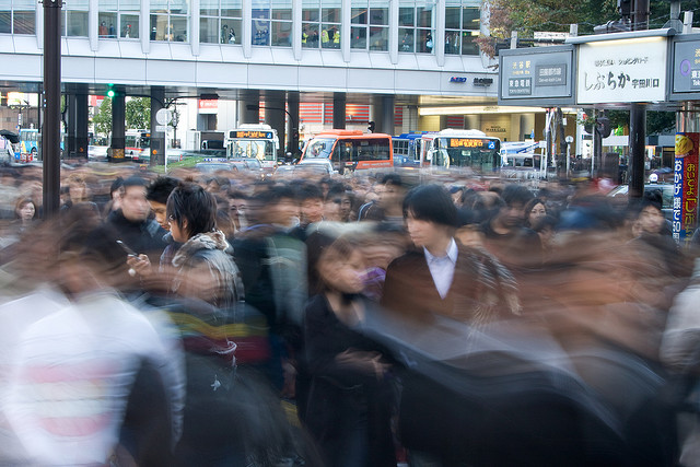 Two of Tokyo's youth examine their smartphone outside Shibuya Station