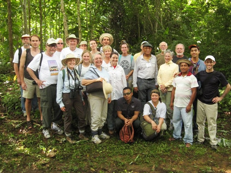 The group poses for a photo in front of the Arimae #3 finca