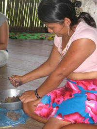An indigenous woman in Arimae mixes jagua ink