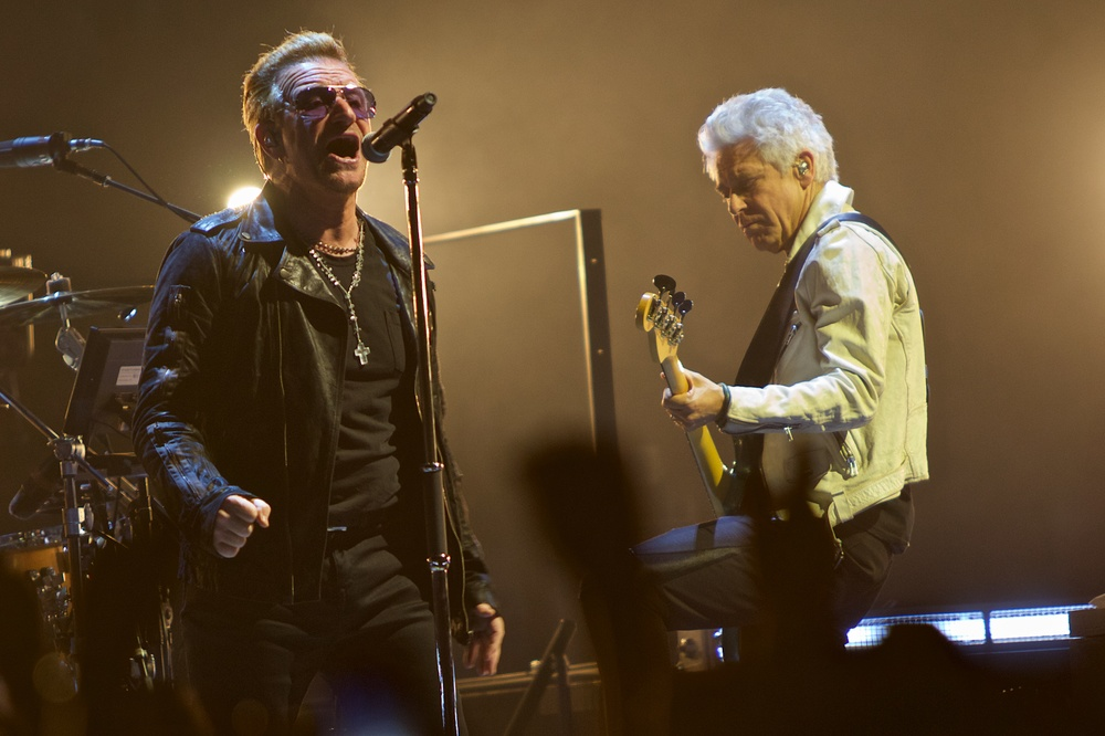 Bono sings while bassist Adam Clayton jams along. (Photo Credit: Robert Castro)