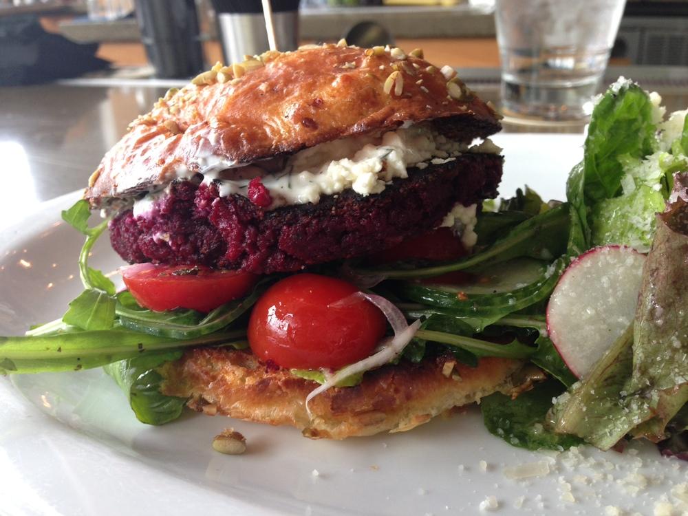 Beet & Walnut Burger -cherry tomato, cucumber, red onion, arugula, feta cheese, lemon Greek yogurt, oregano vinaigrette on pepita brioche.