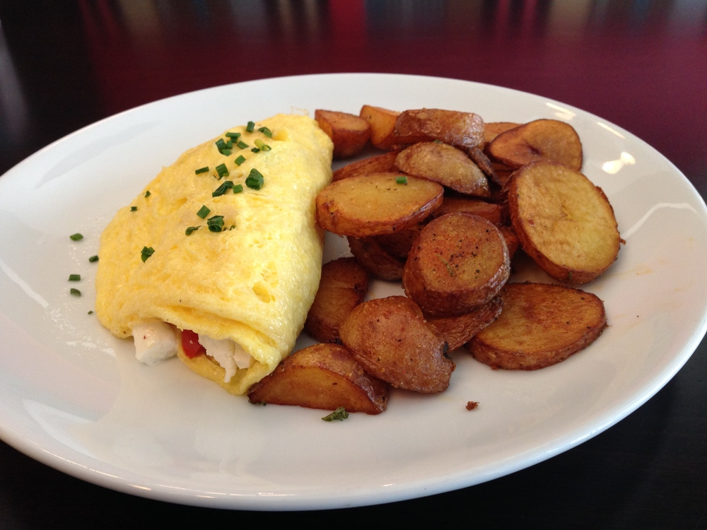 Brunch Club Omelet - filled with sautéed zucchini, onions, roasted red peppers, prosciutto, and goat cheese. Served with breakfast potatoes.