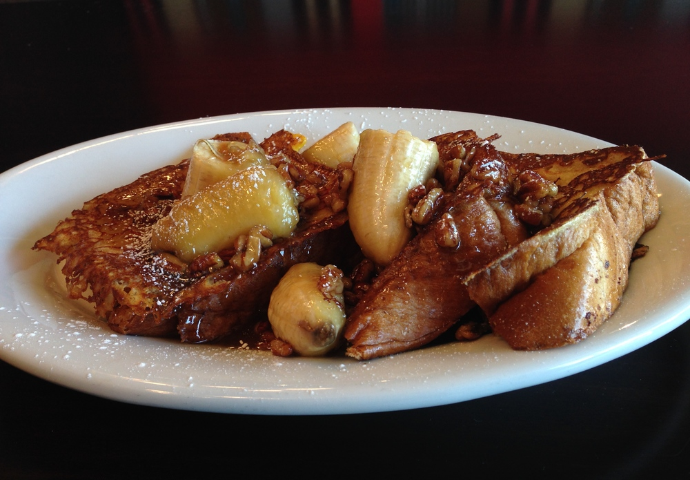 Bananas Foster French Toast - egg batter-dipped Challah bread, topped with bananas brown sugar rum sauce and pecans.