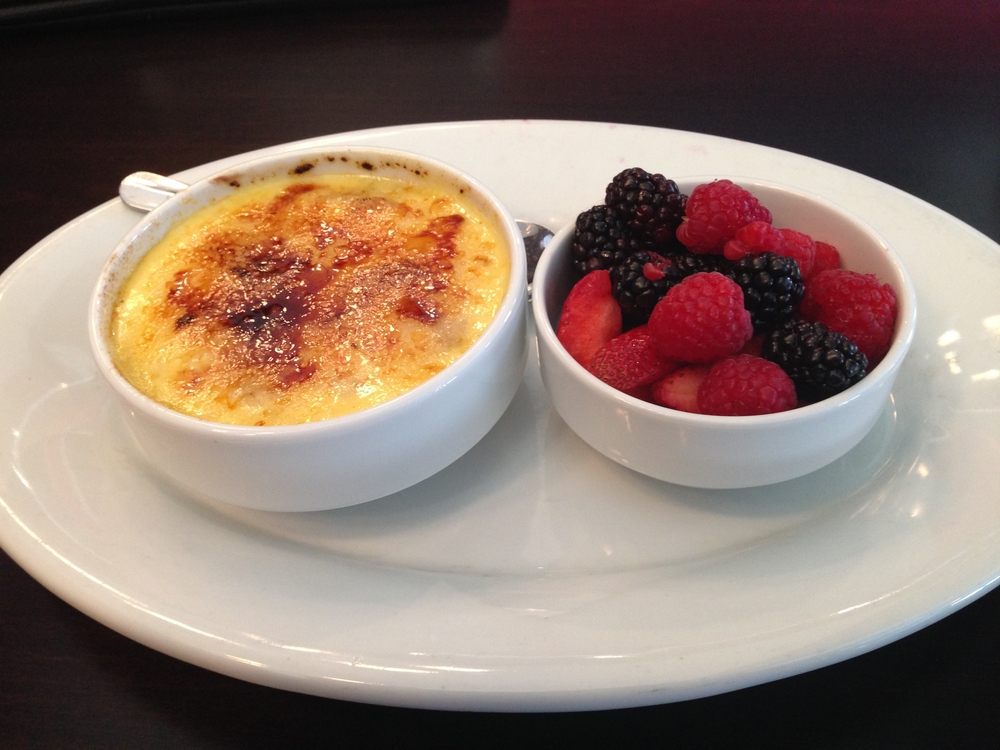 Oatmeal Creme Brûlée - a bowl of steel cut oats topped with vanilla custard and a bruleed sugar crust. Served with fresh berries.