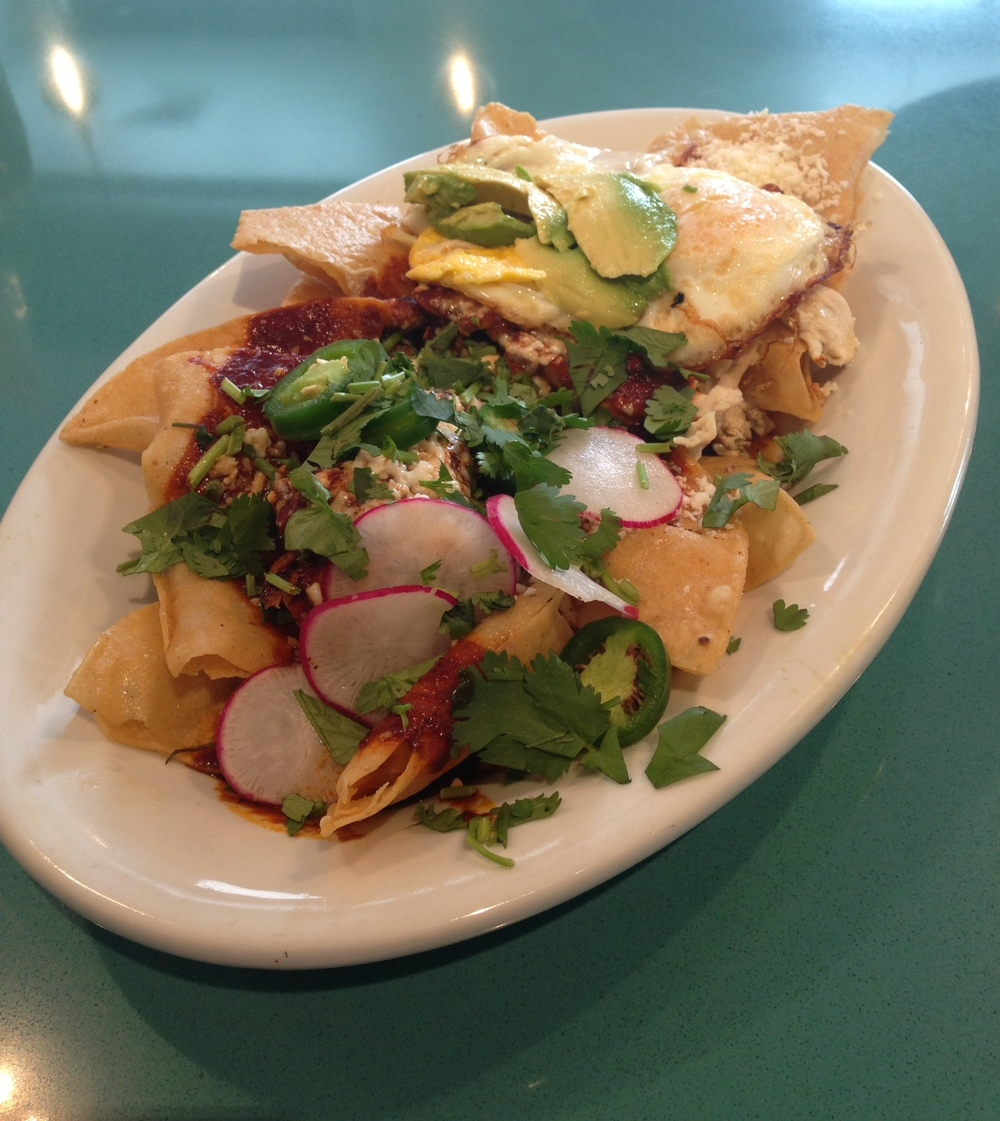 Chilaquiles - corn tortilla chips topped with braised chicken, quajillo chili sauce, queso fresco, avocado, jalapeño, cilantro, radish, and two eggs over-easy.