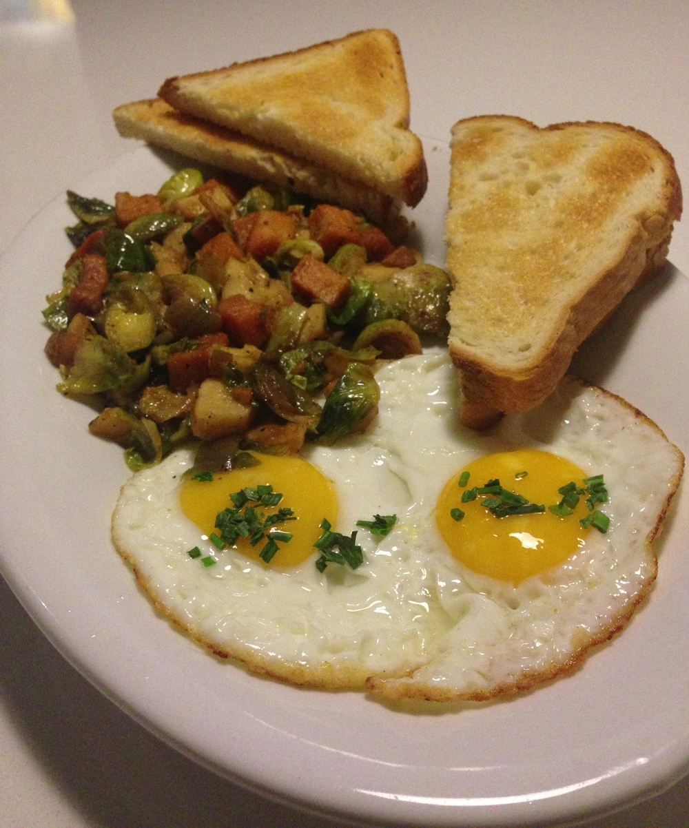 Farmer's Hash - roasted sweet potatoes, brussels sprouts and parsnips sautéed with onion and rosemary and topped with two eggs. Served with toast.