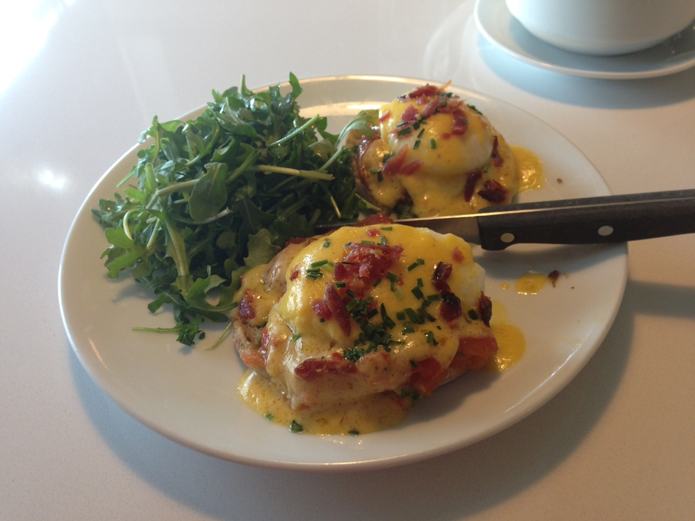 Egg Benedicto -  two poached eggs on a toasted English muffin with roasted tomatoes, Italian salsa verde, sun-dried tomato hollandaise, and crunchy candied prosciutto.