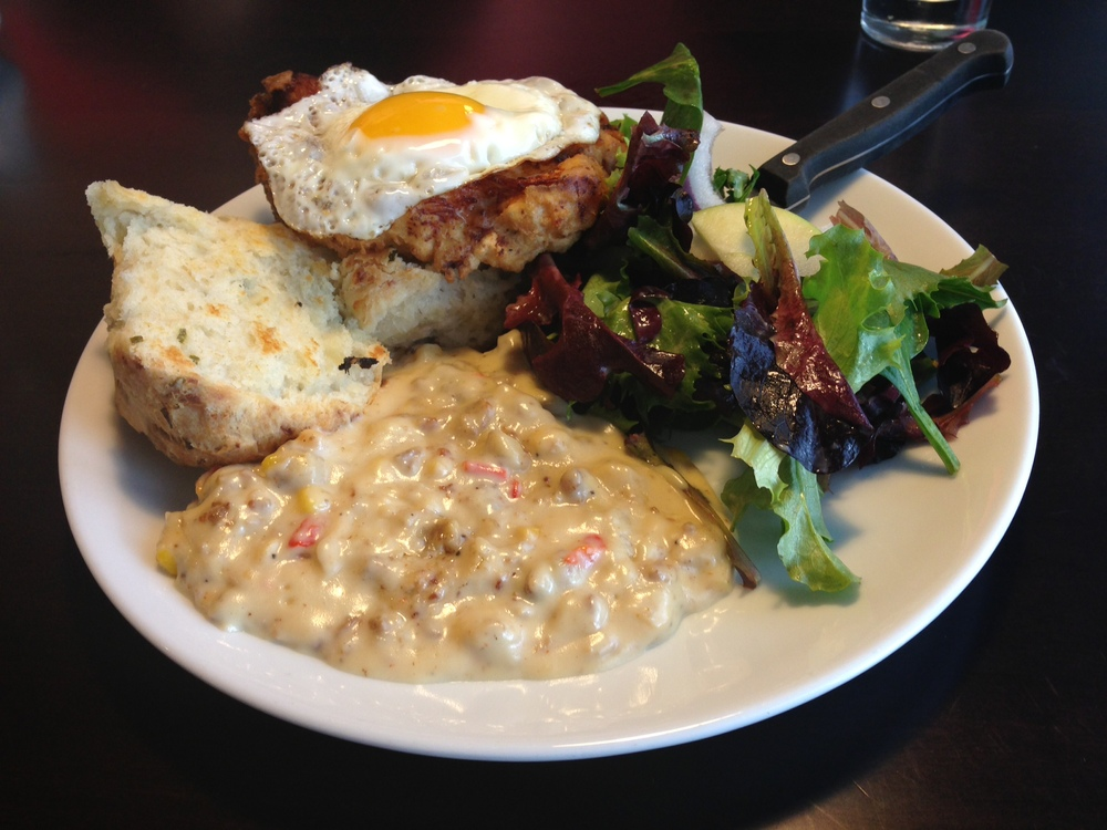 Chicken & a Biscuit - fried white meat chicken topped with a sunny side up egg and served with a homemade biscuit, sweet corn-sausage gravy, and an apple-bacon salad.