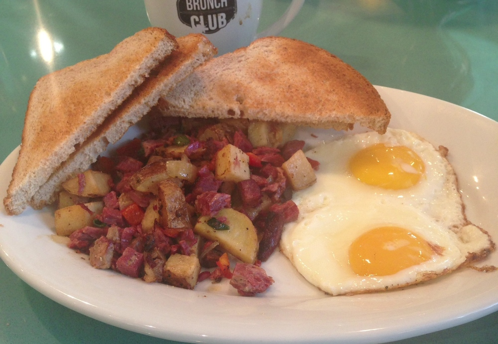 Corned Beef Hash - housemade corned beef, yukon gold potatoes, bell peppers and onion, topped with two eggs. Served with toast.
