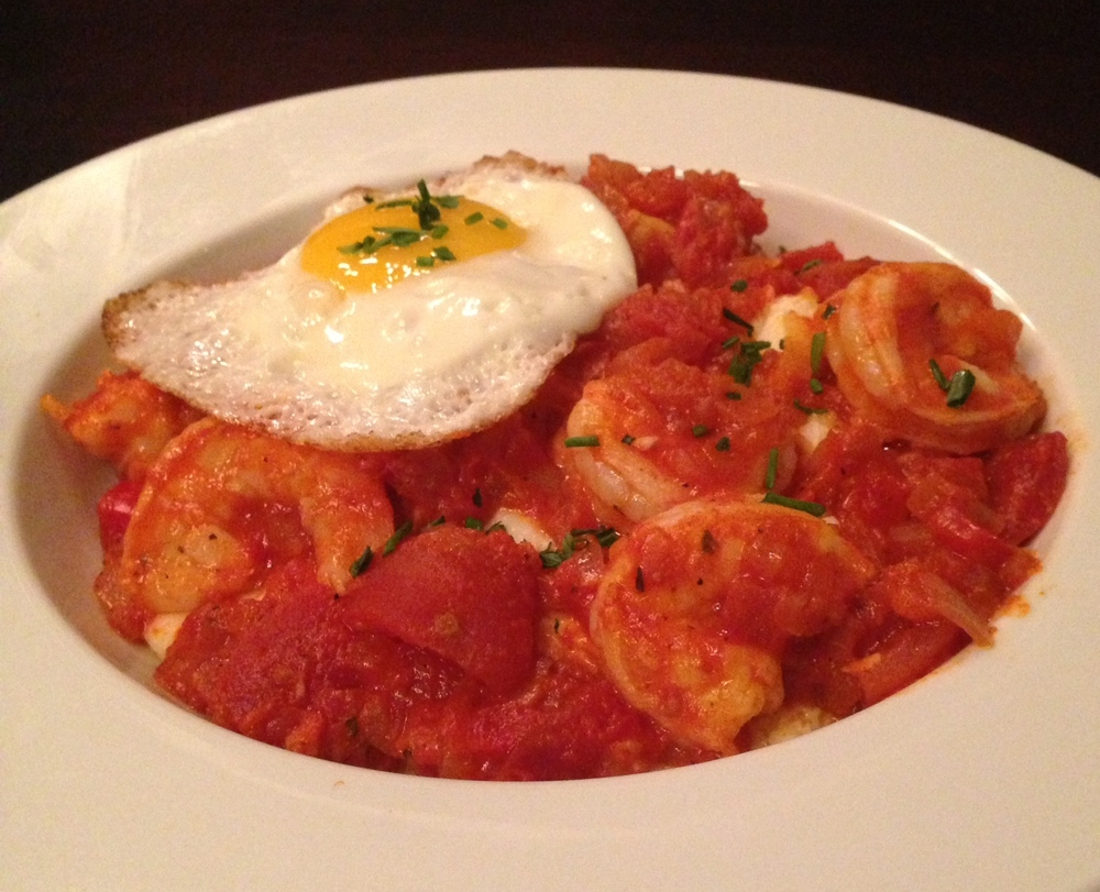 Shrimp & Grits - parmesan white corn grits, sautéed Texas Gulf shrimp. garlicky tomato sauce, and green onions. Topped with a sunny side up egg.