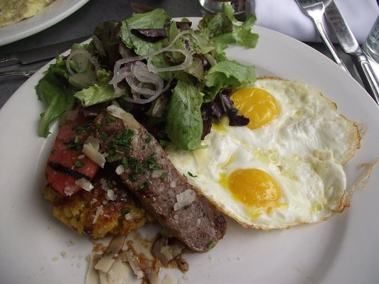 Grilled pork sausages with crispy saffron, zucchini and squash risotto, Grana Padano, two eggs any style and mixed greens
