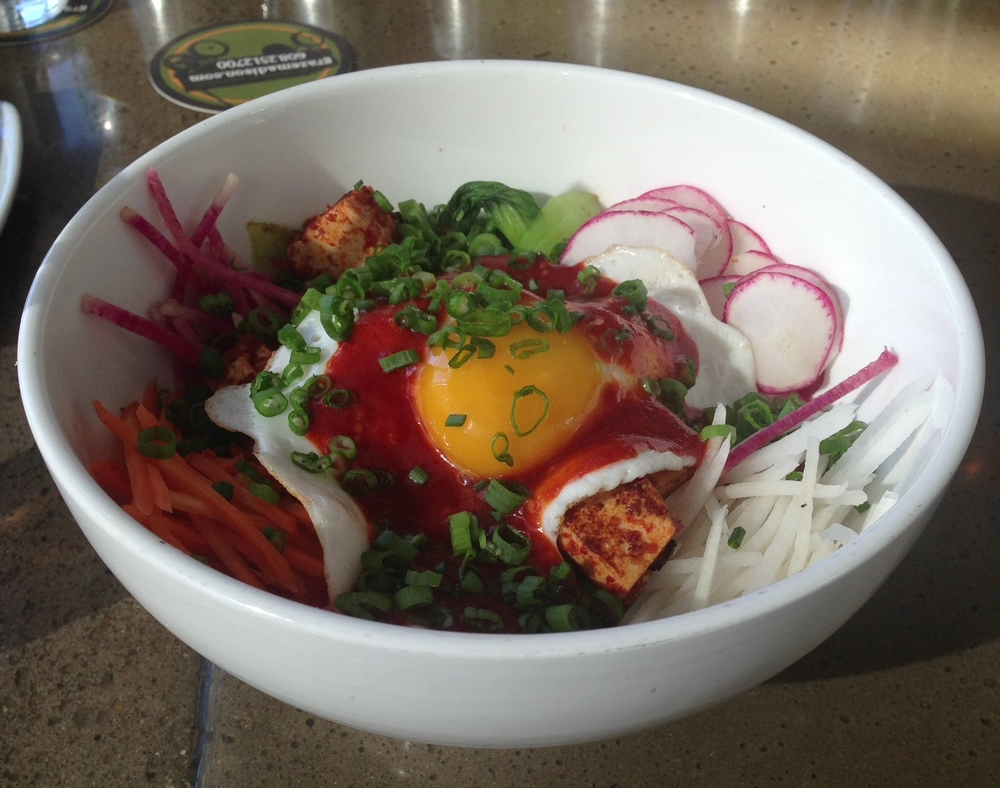 Bibimbap - choice of marinated ground pork or tofu, crispy rice, sunny-side-up egg, market vegetables, spicy gochujang.