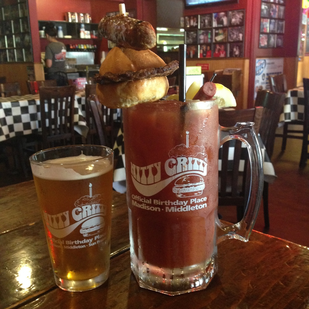 "Brunchzilla - ""This monster is one liter of our house Bloody Mary with Three Olives Vodka, garnished with a sausage link, slice of thick cut hickory smoked bacon, cheese curd, pickle and olive. We top it off with a mini version of our Famous Gritty Burger and serve it with any pint beer chaser of your choice."""