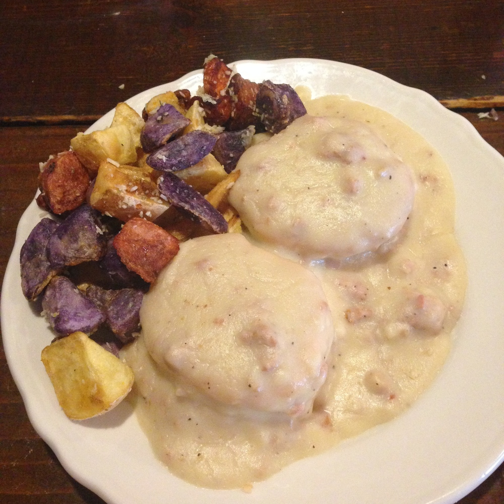 Biscuits and gravy with a side of breakfast potatoes.