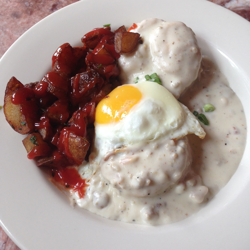 Biscuits & Gravy - cornmeal and buttermilk biscuits with sausage gravy and side of potatoes. Topped with an egg