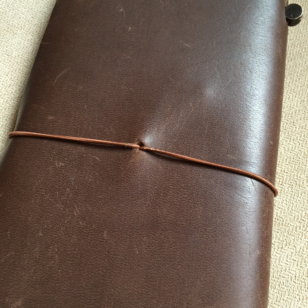 The back of the notebook. Here you can see the elastic band that holds the notebook closed emerging from the center of the back cover.