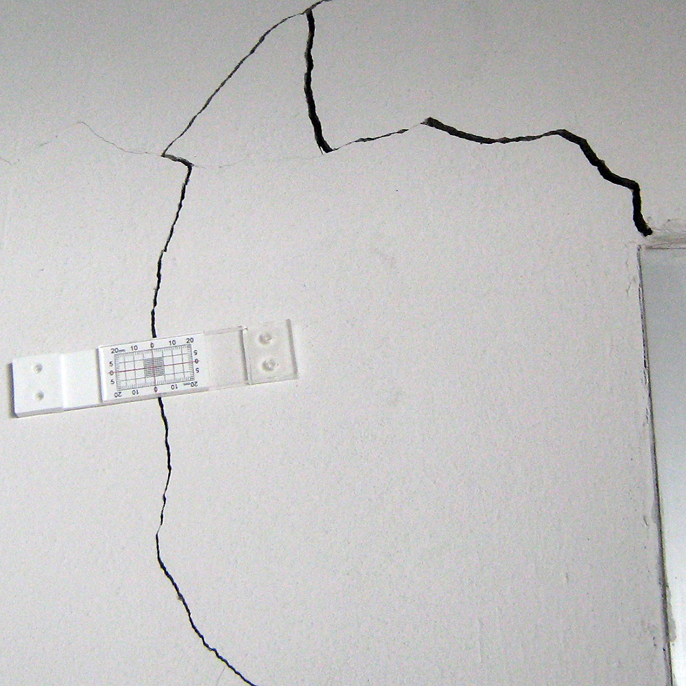 Figure 4. TAMCO engineer installed Buildera CRACKMON® 2D Crack Monitor over shear-wall crack adjacent to door frame