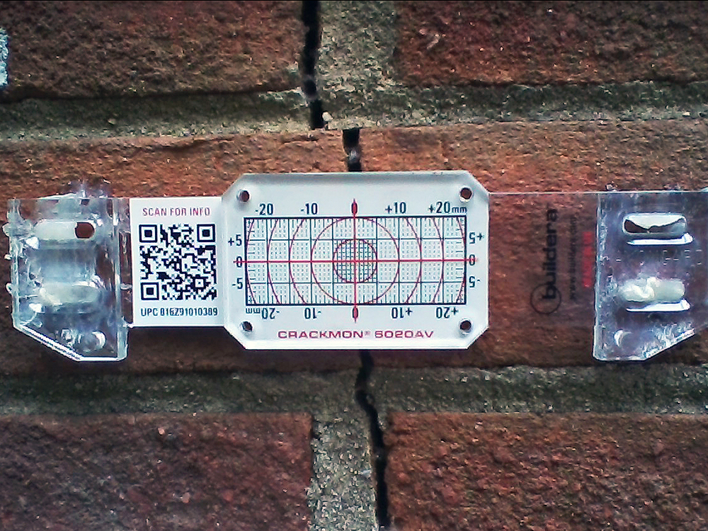FIGURE 5. Buildera CRACKMON 5020AV crack monitor installed at position No. 3 on South wall utility room (slab on grade). Initial crack width varies between 0.120 and 0.140 inches (3.05 to 3.56 mm). Inside caliper measurement reference: 4.583 inches.