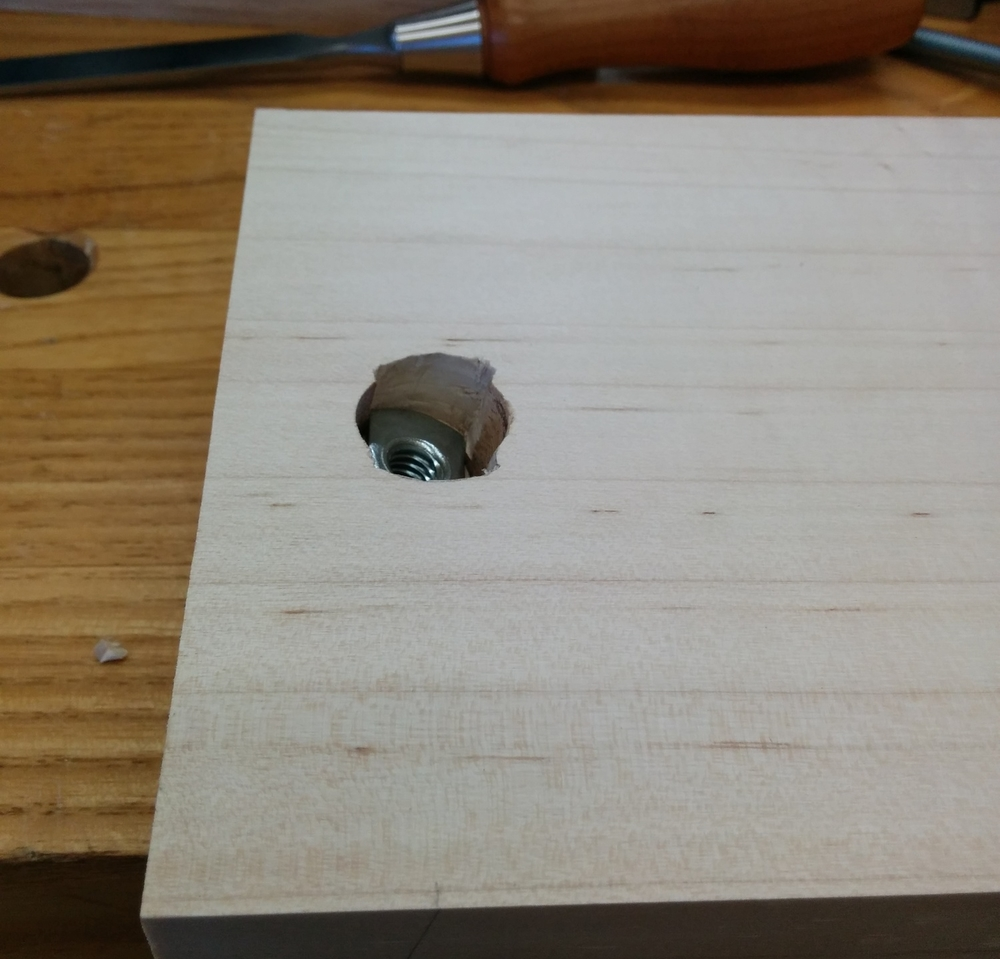 """Here you can see the detail of the sliding T-nut installation. The holes are drilled 13 degrees from vertical so that the adjuster is perpendicular to the support block when it is level. I drilled three holes to install this: 1st=diameter of acorn nut and deep enough so that it can recede into the board, 2nd diameter of the barrel of the t-nut and deep enough for the whole barrel, 3rd the 5/16"""" hole all the way through for the bolt."""