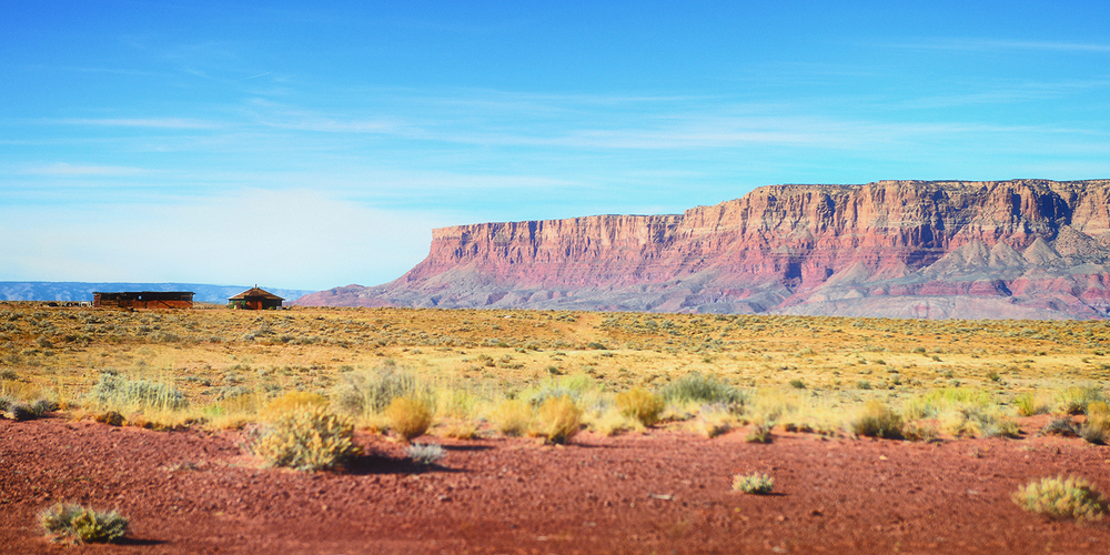 A small primitive house and horse stall sit in the shadows of the Vermillion Cliffs.