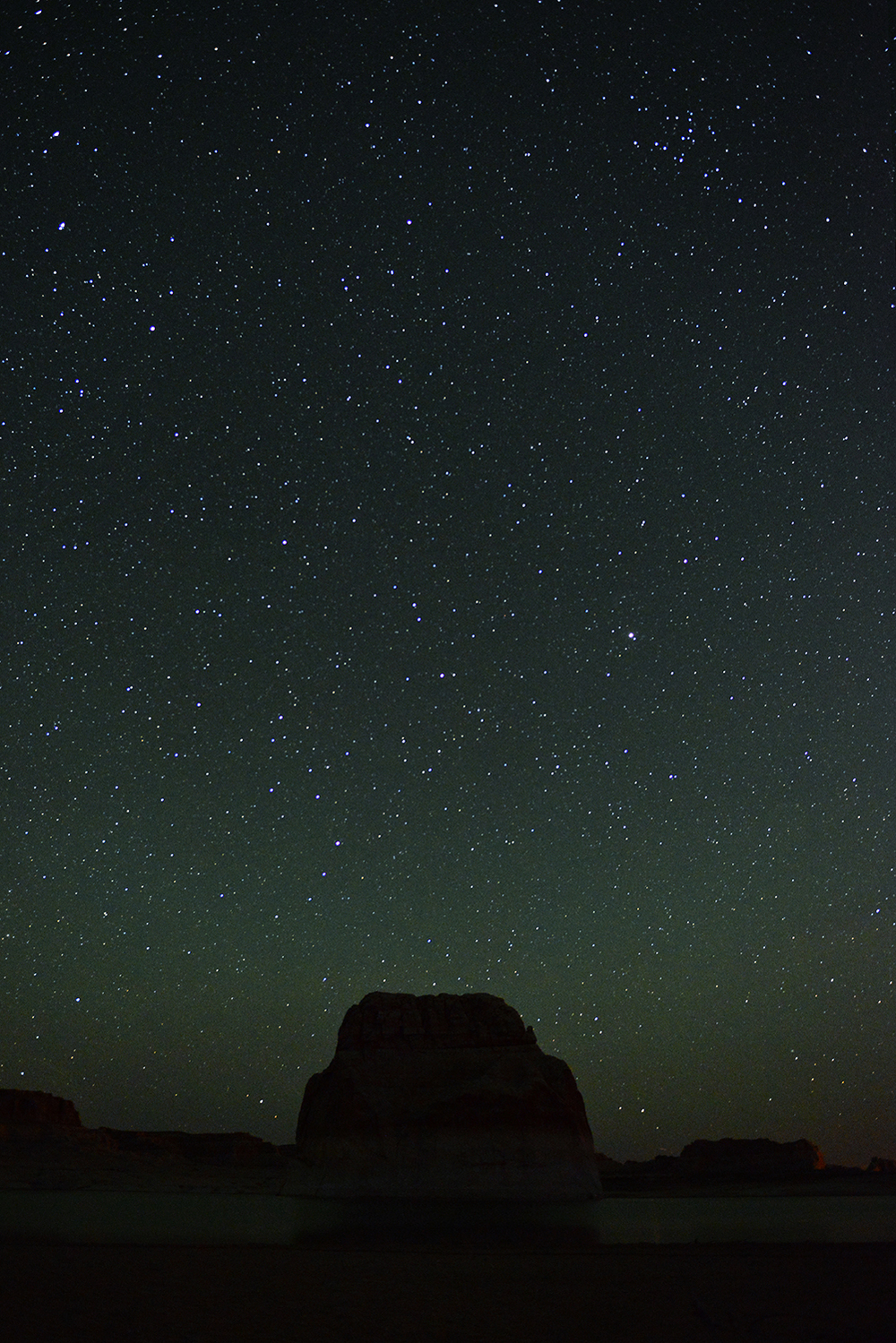 Lone Rock sits alone in the beautiful (and extremely clean) Lake Powell under a sky full of stars.