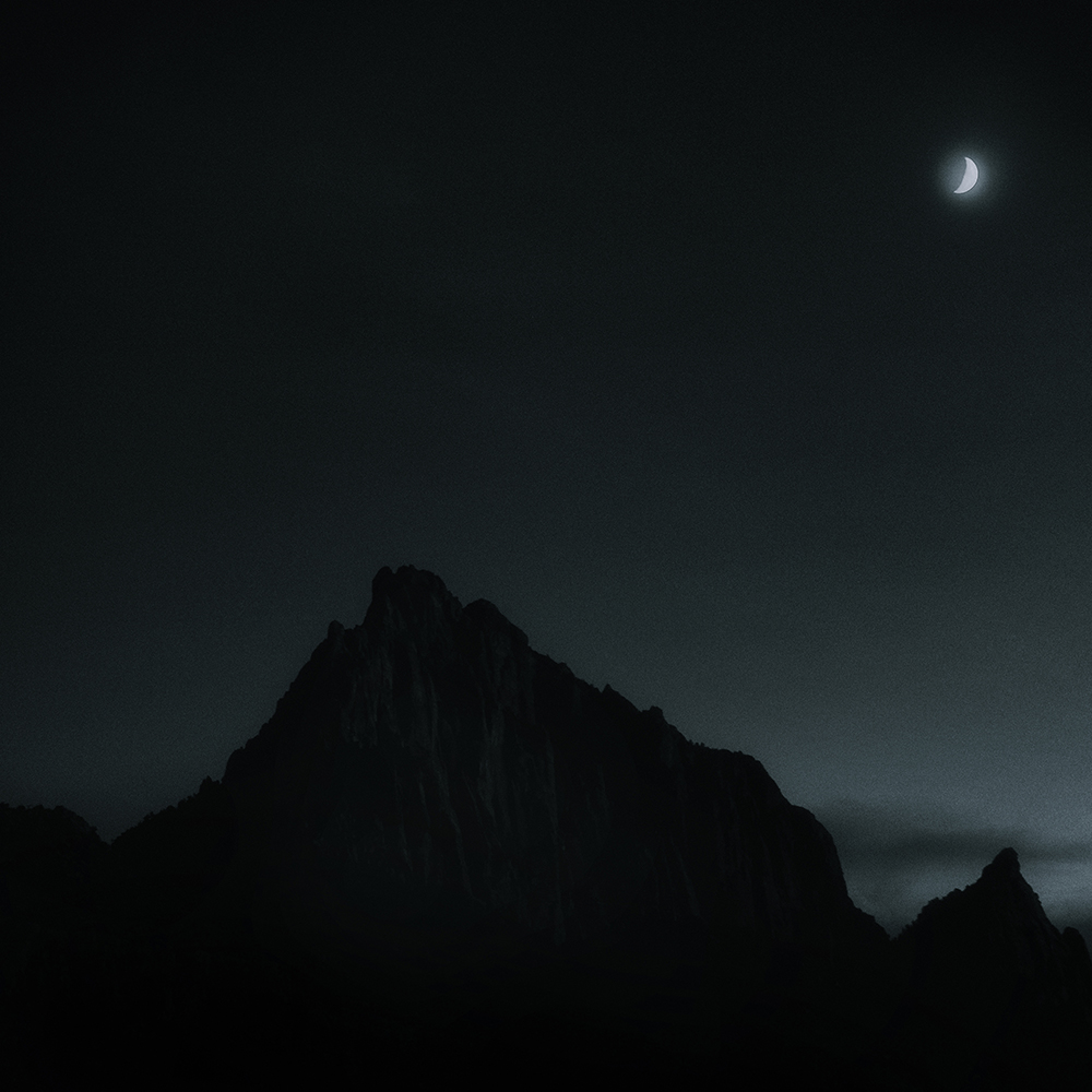 A crescent moon rises above the Watchmen Mountain.