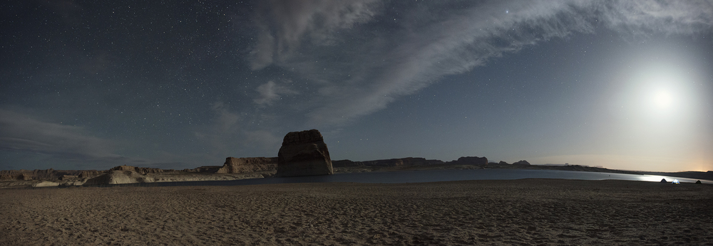 A six shot panorama of Lone Rock Beach. The moon hangs above our tiny tents on the horizon to the right, while the stars shine above Lone Rock and the many sandstone cliffs below.