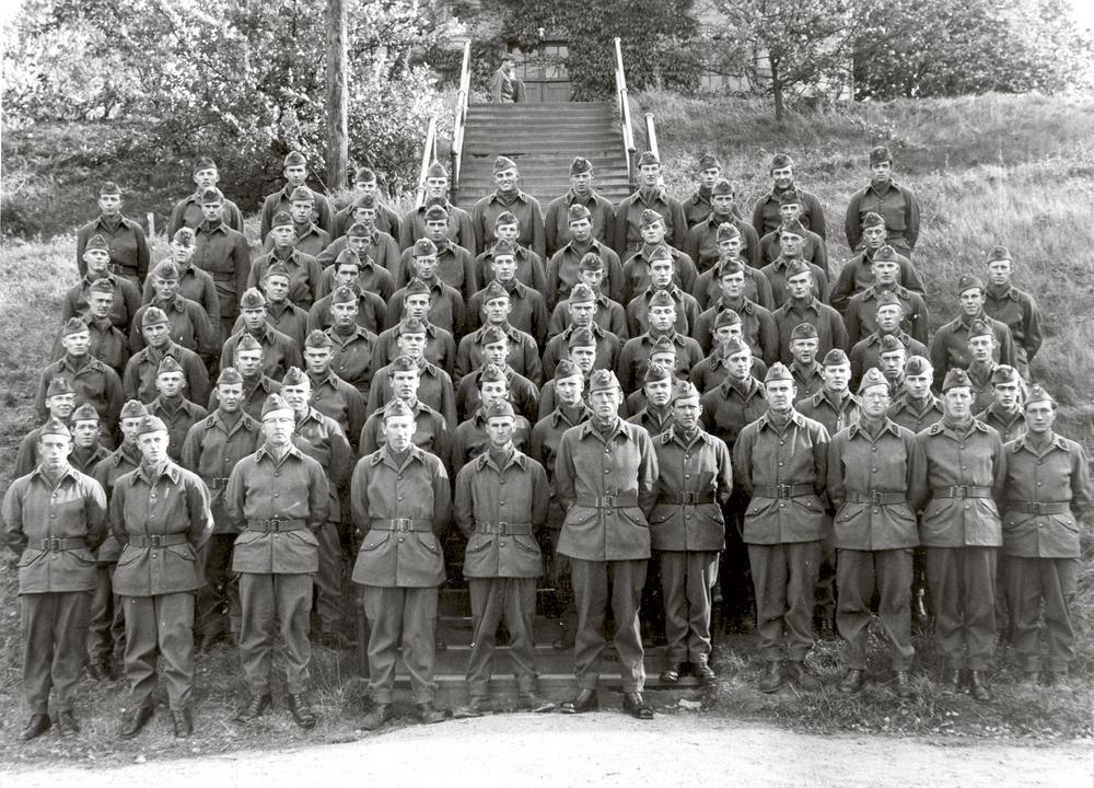 Grundutbildning 1956-1957 Befälen nederst från vänster; Svensson, Furenius, Löjtnant Olivenbaum, Flaggjunkare Dahlén, Löjtnant Högelin, Major Carleson - Kompanichef, Jonasson, Sundberg, Löjtnant Magnusson, 1:a pluton, alltid lika prydlig, Flaggjunkare Hårdsten, 1:a pluton, Mul 10:ans obestridde befälhavare, Sergeant Johansson, 1:a pluton, mannen som sprang rakt fram i skogen istället för att välja väg.