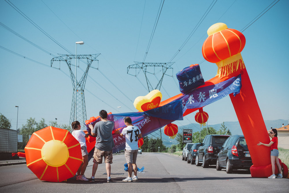 Prato, June 2016. A group of Chinese people prepare the starting line of a marathon taking place in Iolo, an industrial area just outside the town where most of the Chinese fast-fashion businesses are based.
