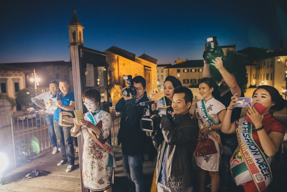 "Prato, July 2016. Models, photographers and reporters attend a photocall at the Castello dell'Imperatore, one of the main landmarks in Central Prato, during ""Prato Fashion Week"", an event promoting local Chinese fast-fashion businesses."