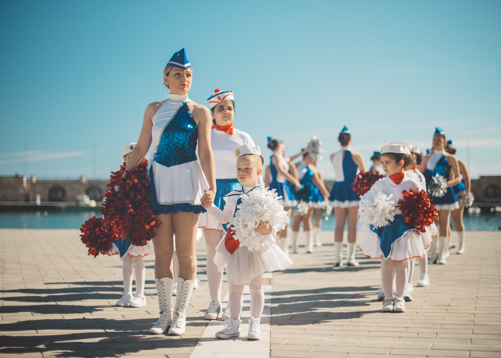 Candida Sabatino, trainer and coach of the Sailors Majorette team, attends to the younger majorettes of the team while leading 4-year-old Miriam, the youngest, by the hand.