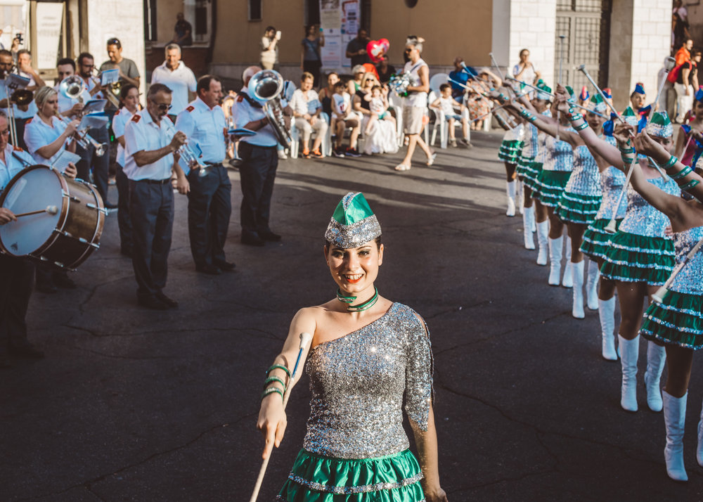 Giulia, captain of the Majorettes Compatrum team, during a performance with a marching band in the main square of Faleria.