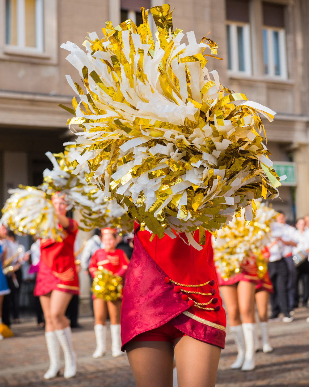 A young majorette performing with pom-poms during a festival of marching bands.