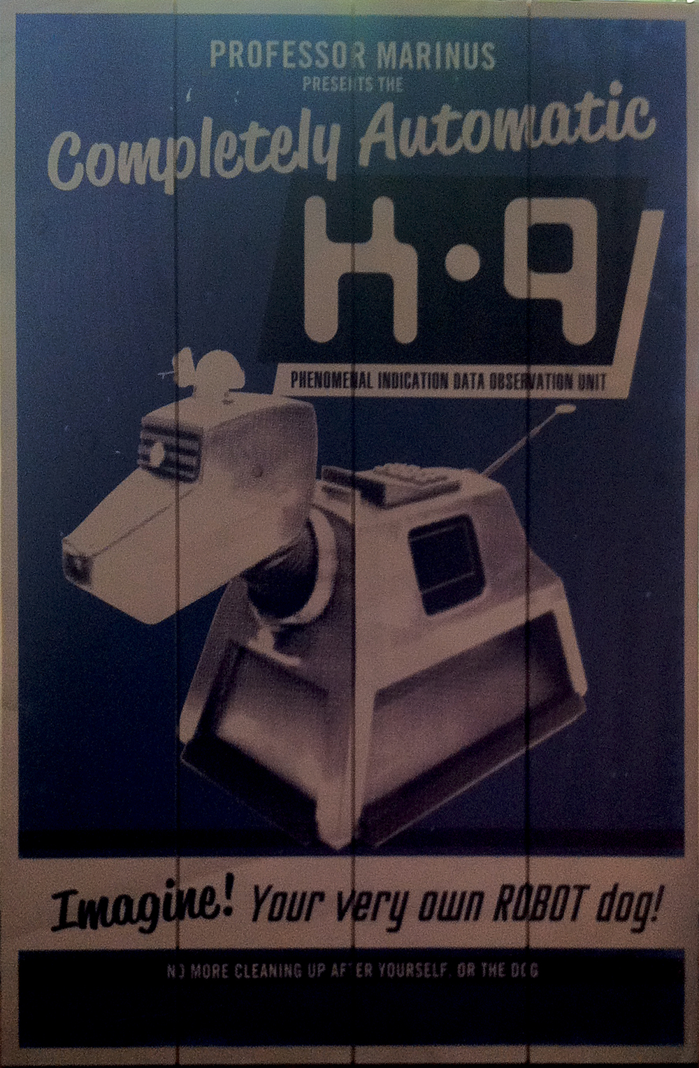 "Image description: A poster that appears to printed on wooden slats. There is an image of K-9, the robot dog from Doctor Who. Text at the top says ""Professor Marinus presents the completely automatic K-9, phenomenal indication data observation unit."" Text at the bottom reads ""Imagine! Your very own robot dog! No more cleaning up after yourself or the dog."""