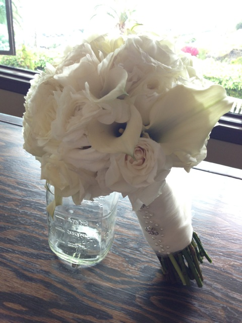 The Bridal bouquet made with garden roses, lisianthus, calla lilies, and ranunculus.  The bouquet was wrapped in ivory satin ribbon with an overlay of mesh and embellished with pearl pins and rhinestone buttons. Lovely.