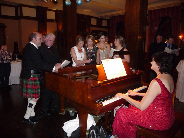 Guests gather at the piano to sing holiday music.