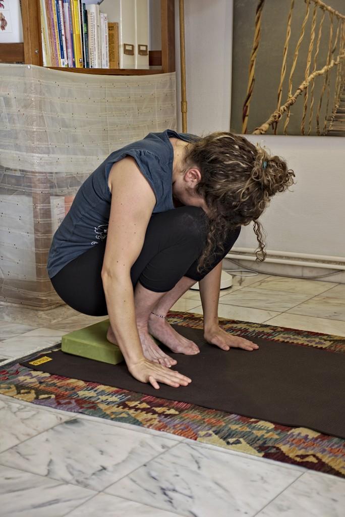 utkatasana  avec support qui rend la posture accessible et réduit le stress sur les genoux.
