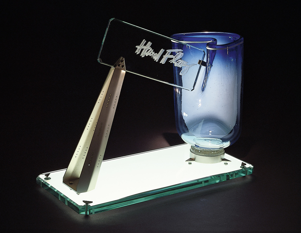 Hard Flag   1980. Blown glass, plate glass, nickel plated brass. 16 x 14 x 8""